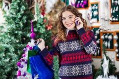 有购物袋的愉快的妇女使用手机 图库摄影