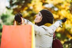 有购物袋的愉快的妇女在秋天 库存图片