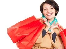 有购物袋的愉快的妇女在米黄秋天外套 免版税库存照片