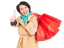 有购物袋的愉快的妇女在米黄秋天外套 库存照片