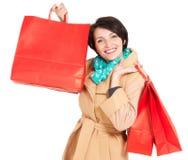 有购物袋的愉快的妇女在米黄秋天外套 图库摄影