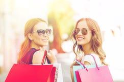 有购物袋的愉快的少妇在城市 库存照片