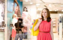 有购物袋的愉快的少妇在超级市场 库存图片