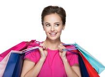 有购物袋的愉快的微笑的妇女在购物以后 图库摄影