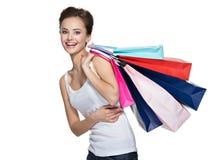 有购物袋的愉快的微笑的妇女在购物以后 免版税库存照片