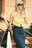 有购物袋的愉快的时尚妇女谈话在手机在购物中心 图库摄影