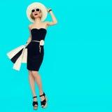 有购物袋的愉快的购物妇女在蓝色背景 免版税图库摄影