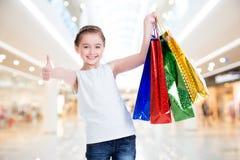 有购物袋的相当微笑的小女孩 免版税库存照片