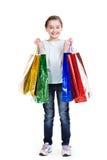有购物袋的相当微笑的小女孩 免版税图库摄影