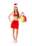 有购物袋的美丽的圣诞老人圣诞节女孩在白色 免版税库存图片
