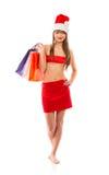 有购物袋的美丽的圣诞老人圣诞节女孩在白色 库存图片
