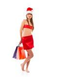 有购物袋的美丽的圣诞老人圣诞节女孩在白色 免版税图库摄影