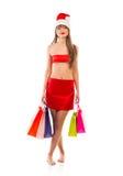 有购物袋的美丽的圣诞老人圣诞节女孩在白色 库存照片