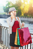 有购物袋的美丽的女孩谈话在手机 免版税图库摄影