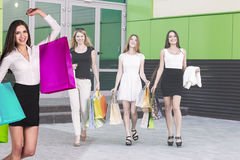 有购物袋的美丽的女孩临近购物中心 库存照片