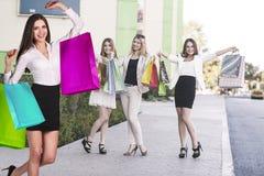 有购物袋的美丽的女孩临近购物中心 免版税库存照片