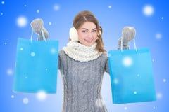 有购物袋的美丽的妇女在雪圣诞节backgroun 免版税库存照片