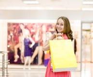 有购物袋的美丽的少妇在超级市场 免版税图库摄影