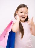 有购物袋的逗人喜爱的女孩 免版税图库摄影