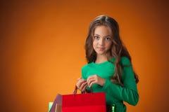 有购物袋的逗人喜爱的快乐的小女孩 库存照片