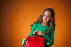 有购物袋的逗人喜爱的快乐的小女孩 库存图片