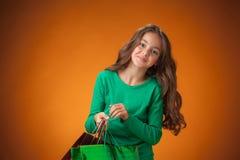 有购物袋的逗人喜爱的快乐的小女孩 免版税库存照片