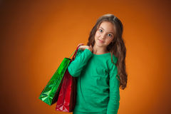 有购物袋的逗人喜爱的快乐的小女孩 免版税图库摄影