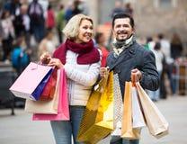 有购物袋的领抚恤金者在城市街道上 免版税库存照片