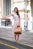 有购物袋的年轻愉快的女孩乘坐一辆出租汽车 站立在街道藏品的一名美丽的愉快的妇女的画象 库存图片