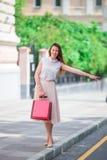 有购物袋的年轻愉快的女孩乘坐一辆出租汽车 站立在街道藏品的一名美丽的愉快的妇女的画象 免版税图库摄影
