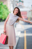 有购物袋的年轻愉快的女孩乘坐一辆出租汽车 站立在街道藏品的一名美丽的愉快的妇女的画象 免版税库存图片