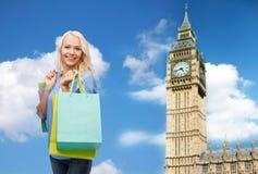 有购物袋的年轻愉快的妇女在大笨钟 库存照片