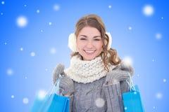 有购物袋的年轻美丽的妇女在雪圣诞节bac 免版税库存照片