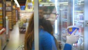 有购物车买的牛奶店的少妇或在超级市场的被冷藏的杂货被冷藏的部分的 影视素材