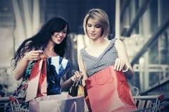 有购物车的两名年轻时尚妇女在购物中心 图库摄影