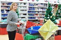 有购物车的美丽的妇女在圣诞节的s超级市场 免版税库存照片