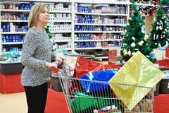 有购物车的美丽的妇女在圣诞节销售的超级市场 库存图片