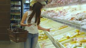 有购物车购买的妇女冷藏了杂货在超级市场和使用片剂个人计算机检查购物单女孩 股票录像