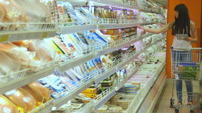 有购物车购买的少妇冷藏了杂货在超级市场和使用片剂个人计算机检查购物 股票录像