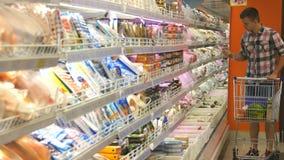有购物车购买的年轻人在被冷藏的部分的超级市场冷藏了杂货 人过来 影视素材