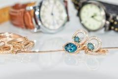 有黄玉的金耳环在端庄的妇女` s watche背景  免版税库存图片