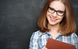 有玻璃和书的愉快的女学生从黑板 库存照片