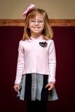 有玻璃和弓的微笑的女孩 免版税库存图片