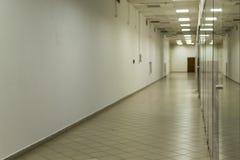 有玻璃和白色油漆的离开的空的走廊 免版税库存照片