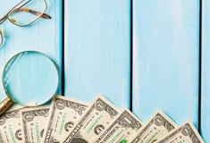 有玻璃和美金的放大镜在蓝色木背景 免版税库存照片