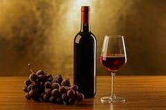 有玻璃和葡萄的红葡萄酒瓶在木桌和金背景 库存图片
