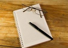有玻璃和钢笔的笔记本在木书桌上 免版税库存照片