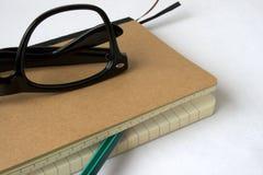 有玻璃和铅笔的笔记本 免版税库存照片