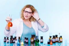 有玻璃器皿测试烧瓶的女性化学学生 库存照片