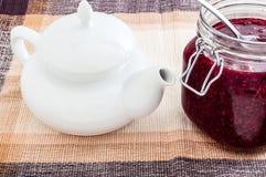 有玻璃容器的茶壶在桌上的果酱 库存图片